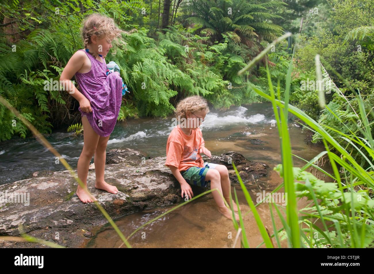 New Zealand, Rotorua, Kerosene Creek, Two Children (4-5) (6-7) on riverbank - Stock Image