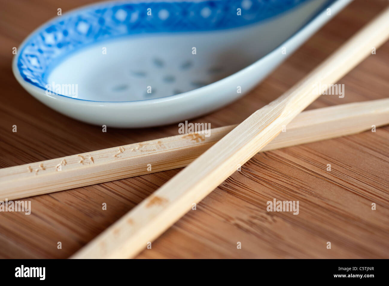 A Pair of Wooden Chopsticks and A Porcelain Chinese Spoon. Shallow DoF. - Stock Image