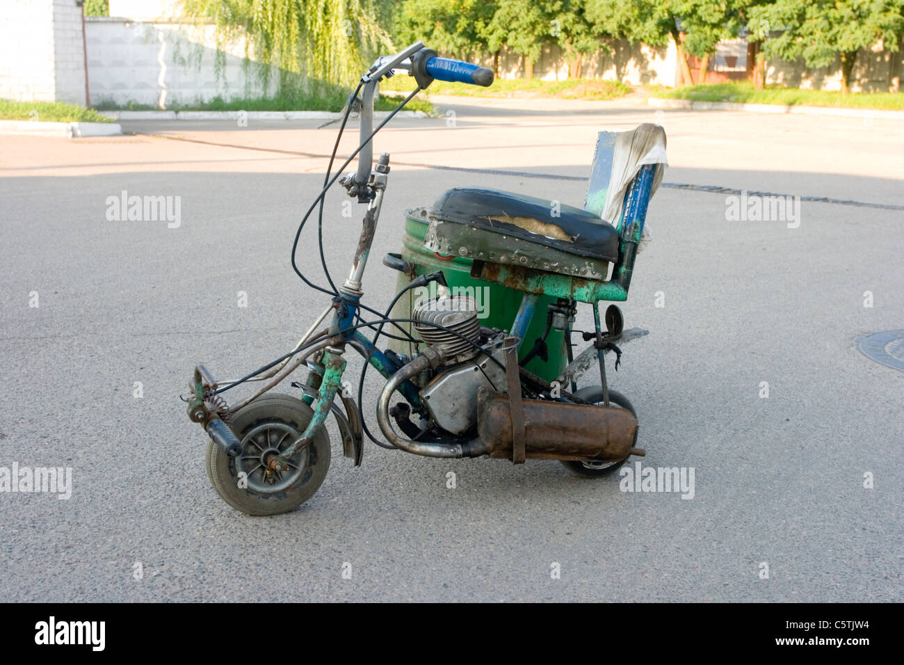 Three-wheeled scooter homemade simple design. Against the background of the asphalt - Stock Image