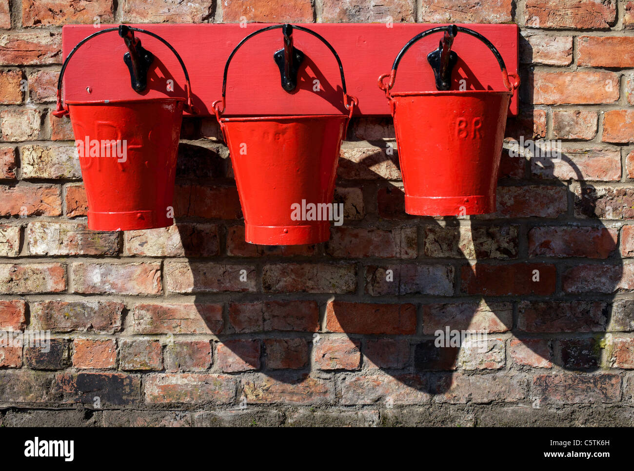 Three wall mounted fire buckets at Levisham Railway Station, Ryedale, North Yorkshire Moors. The station opened - Stock Image
