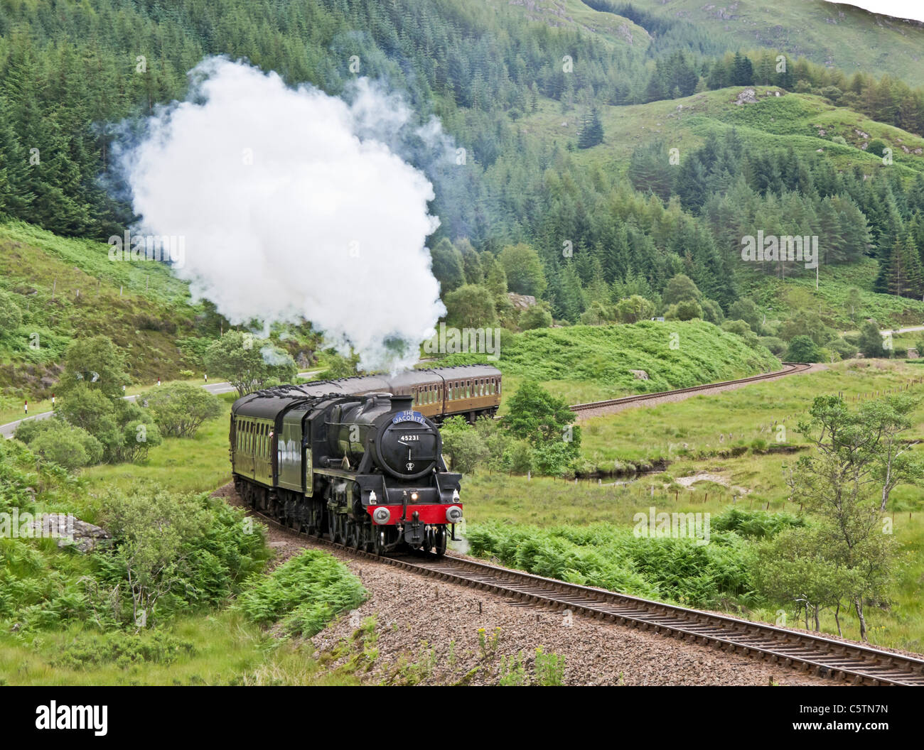 Jacobite steam train moves up hill beyond Glenfinnan Station towards Mallaig on a sunny summer day - Stock Image