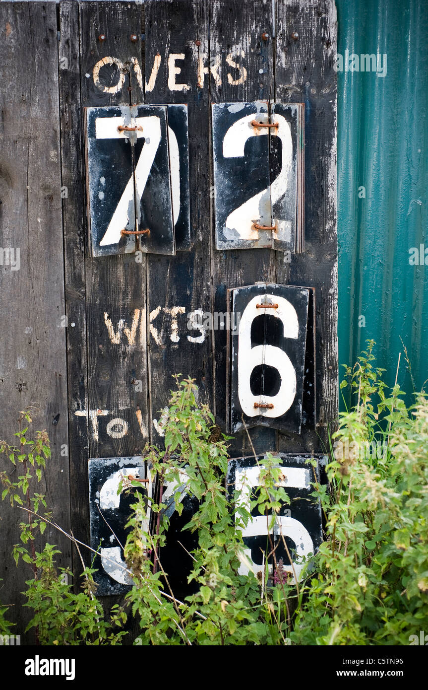 Old cricket scoreboard with weeds, score, play, total, overs Stock