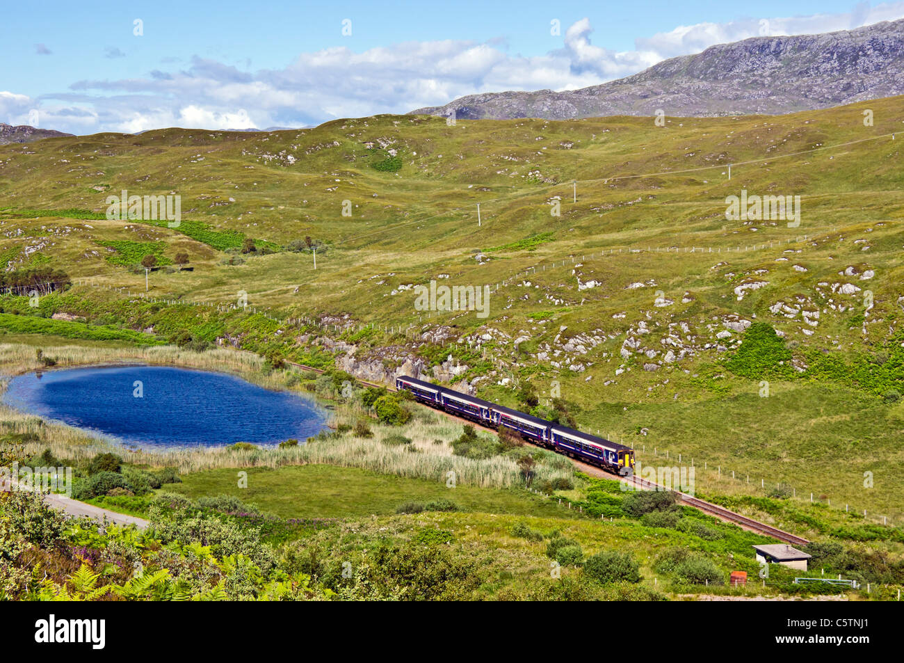 Afternoon class 156 First Scotrail DMU passing small loch before Morar on its journey from Mallaig to Fort William - Stock Image