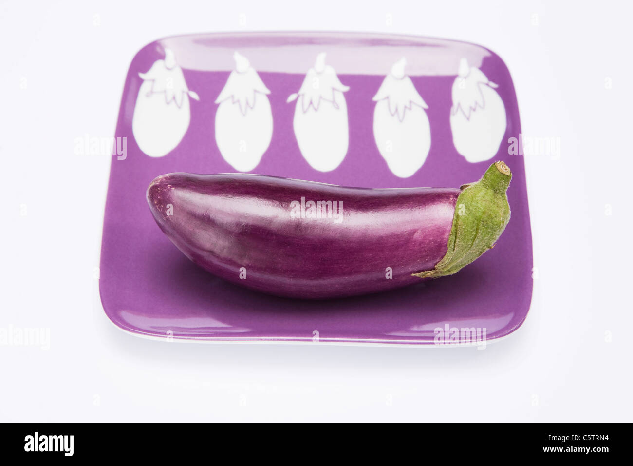 Raw Eggplant (Solanum melongena) on plate Stock Photo