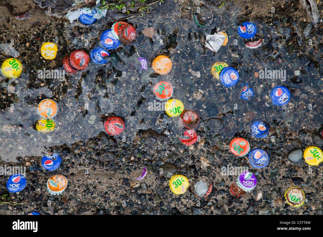 Littering litter bottle caps at beach . - Stock Image