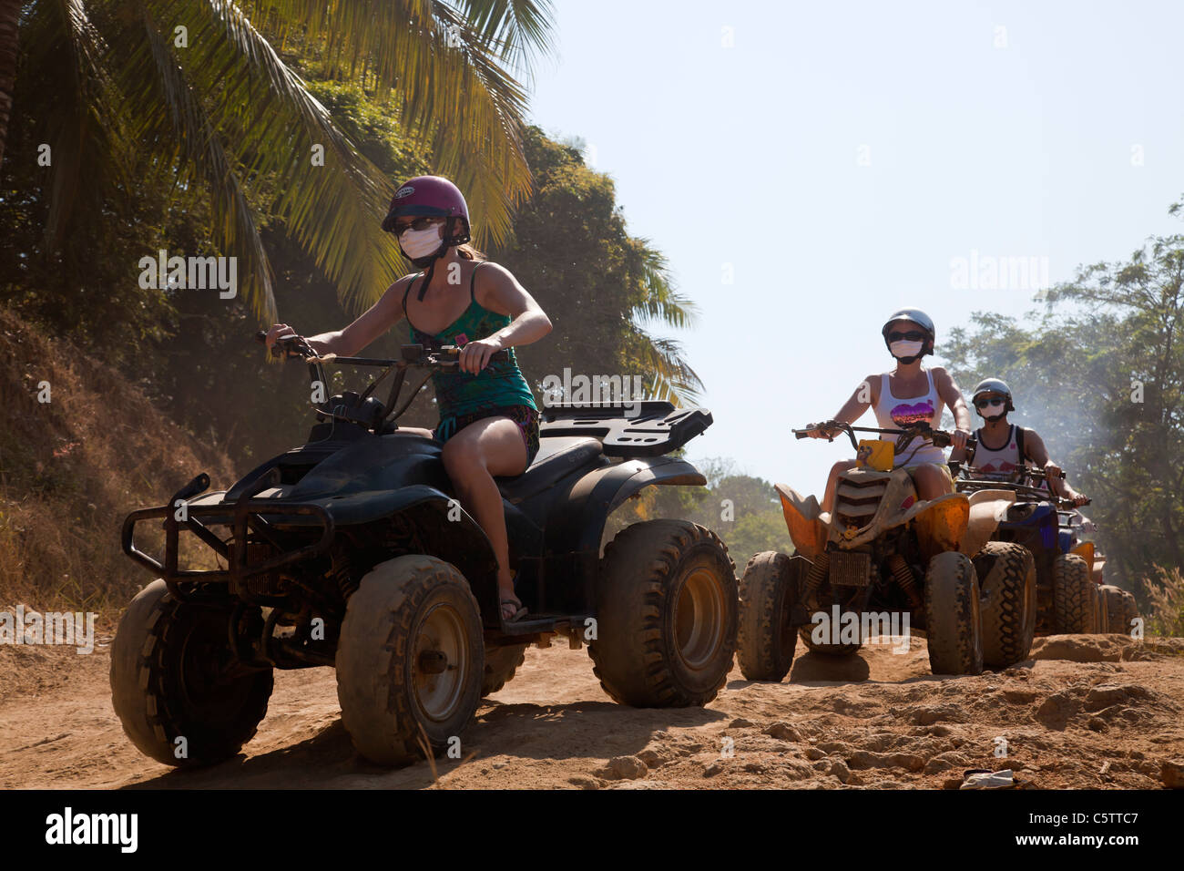 Adventure Tourism Quadrunner tourists on Four-wheel-drive Beach buggies on dirt road. - Stock Image