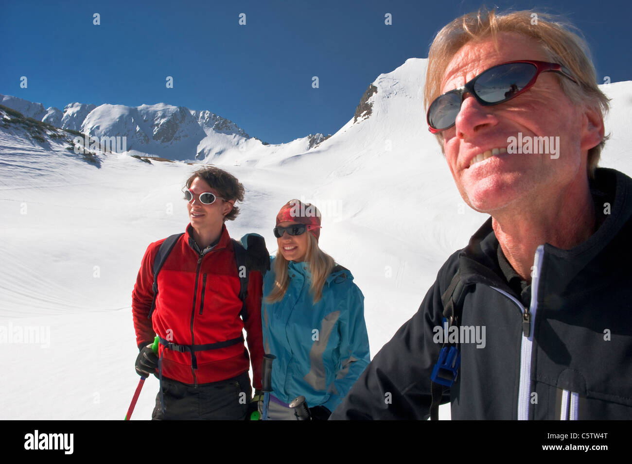 Austria, Salzburger Land, Altenmarkt, Zauchensee, Three persons in snowy landscape, man holding ski pole, portrait - Stock Image