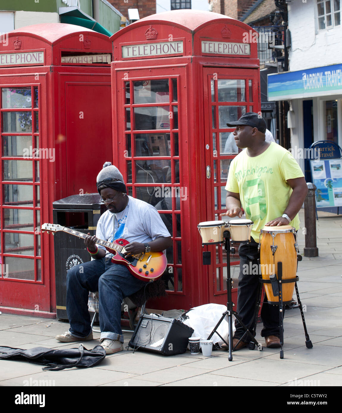 A pair of buskers on a street in Stratford upon Avon, Warwickshire, England, UK. - Stock Image