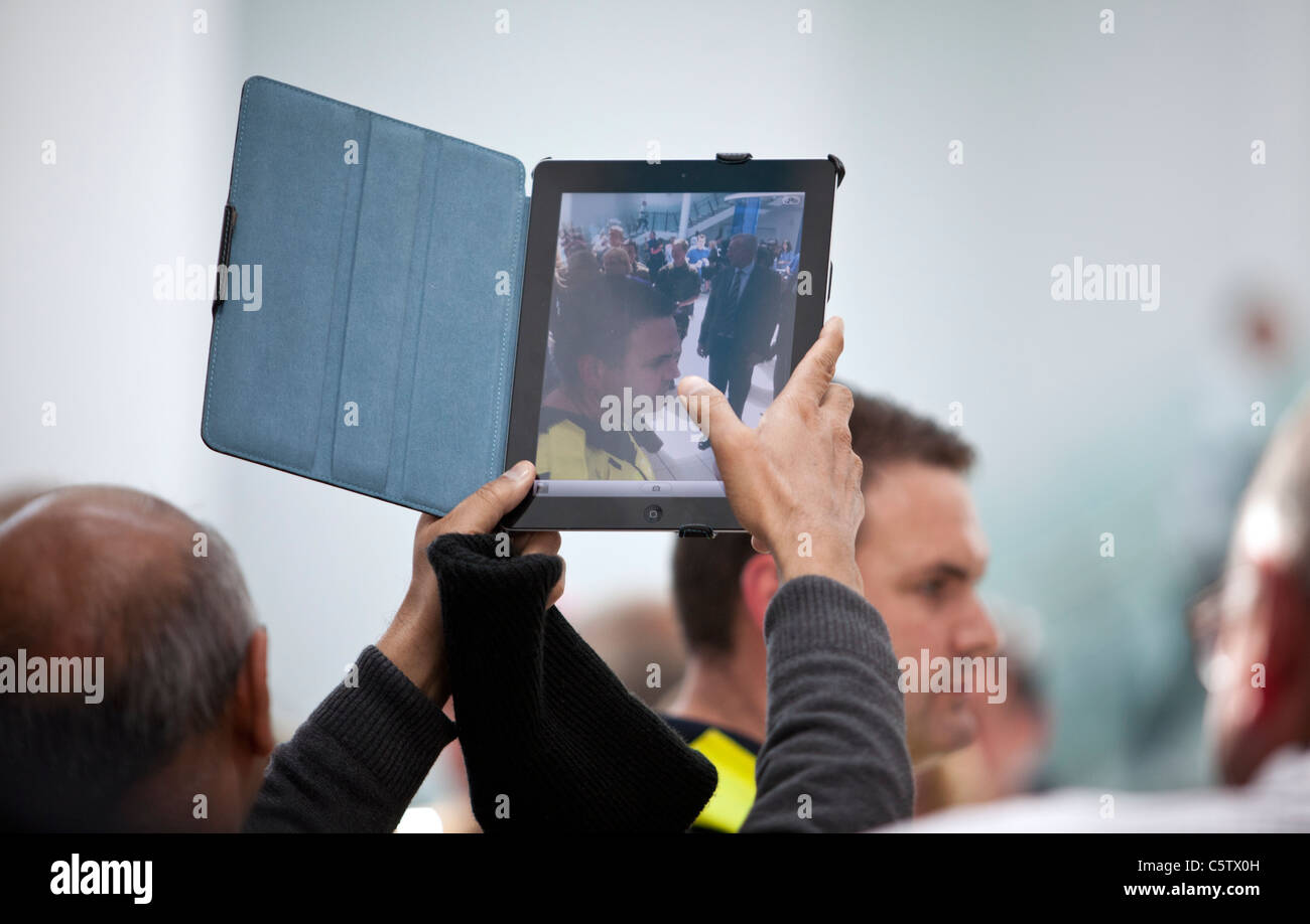 An iPad 2 is held aloft to take a photograph with it's built in camera. - Stock Image