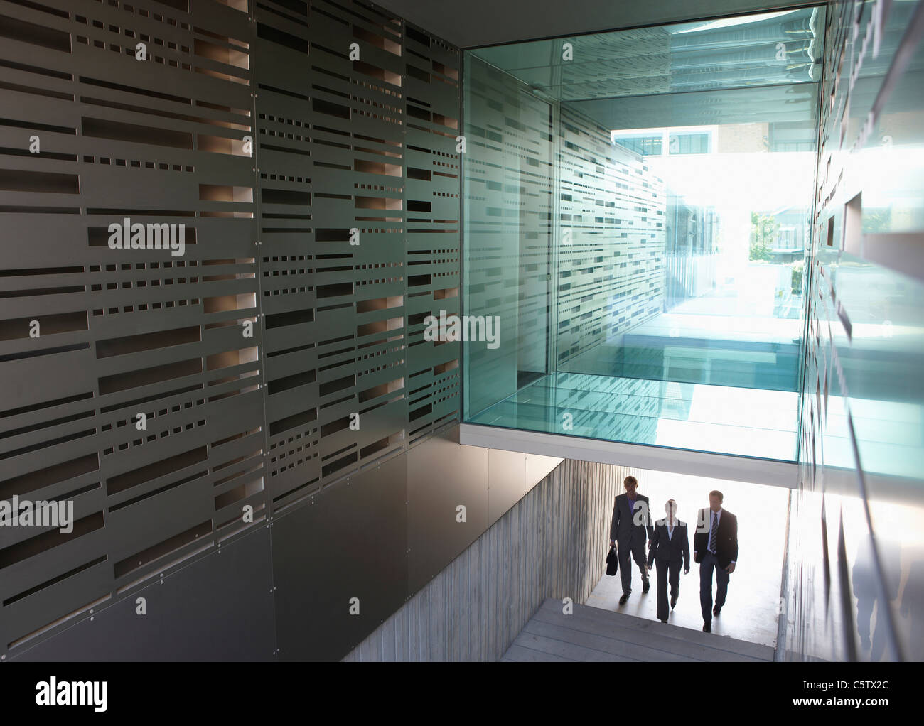 Germany, Cologne, Three business people in staircase, elevated view - Stock Image