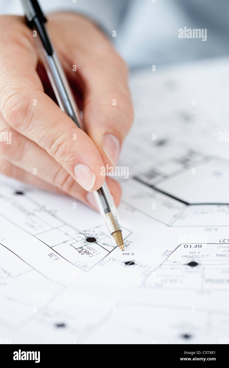 Architect pointing at blueprint with pen, close-up of hand - Stock Image