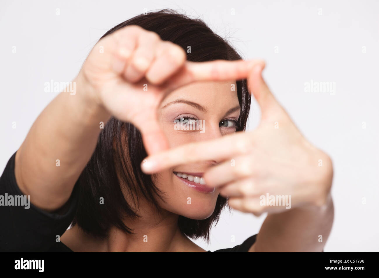 Close up of mid adult woman showing hand sign against white background, smiling, portrait - Stock Image