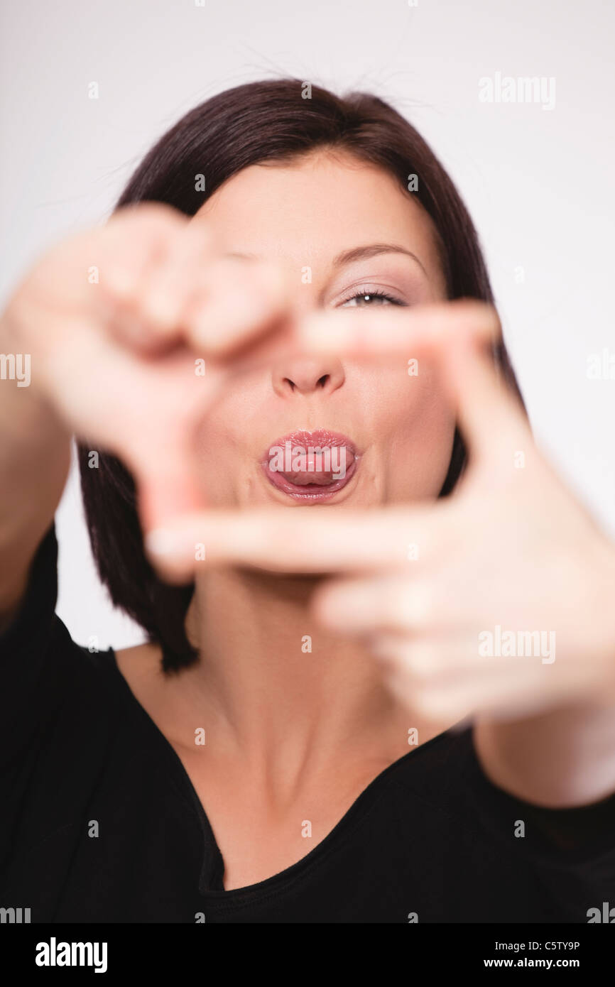 Close up of mid adult woman showing hand sign against white background, portrait - Stock Image