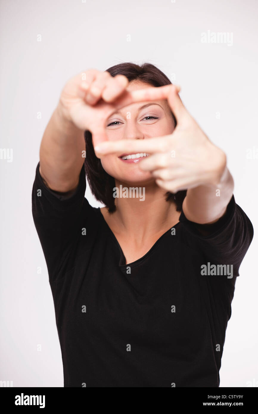 Mid adult woman showing hand sign against white background, smiling, portrait - Stock Image