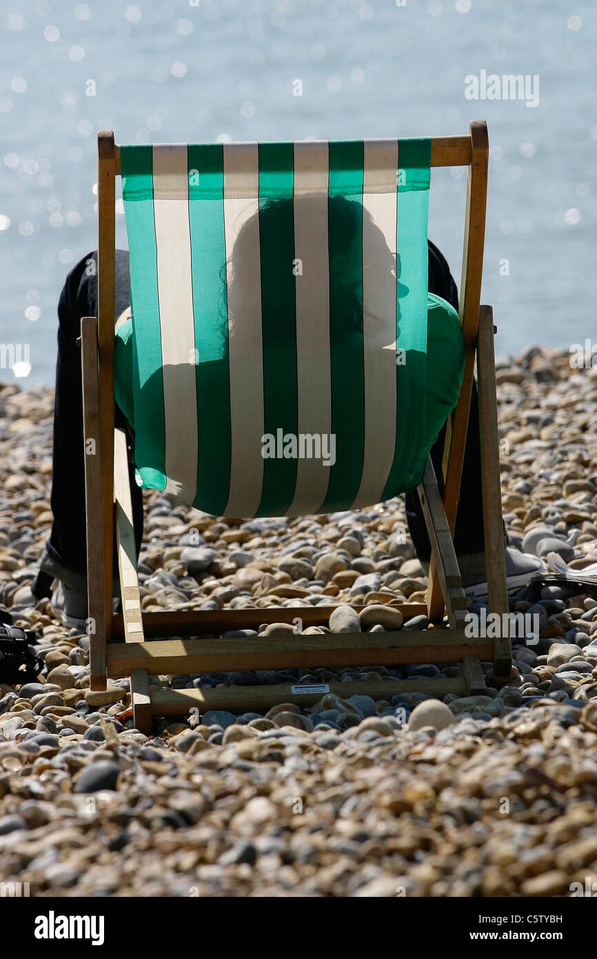 Man sunbathing on Brighton beach in a deck chair. Picture by James Boardman - Stock Image
