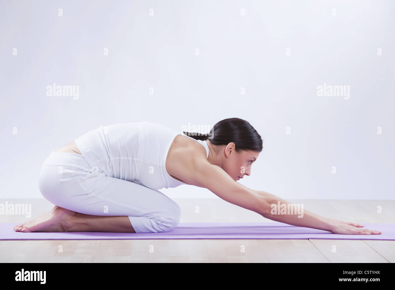 Mid adult woman doing child's pose against white background - Stock Image