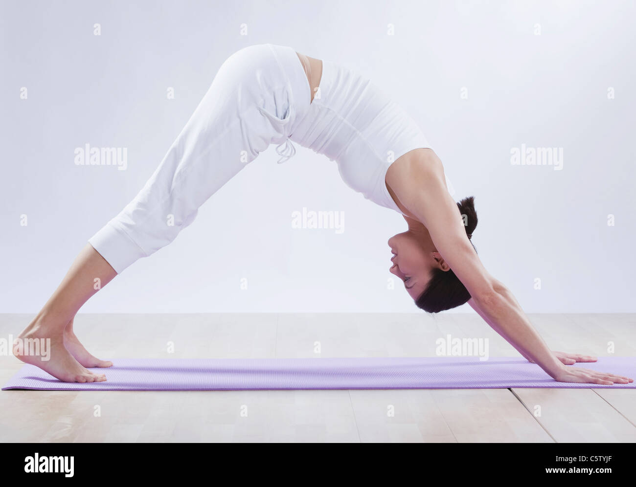 Mid adult woman doing downward facing dog position against white background - Stock Image