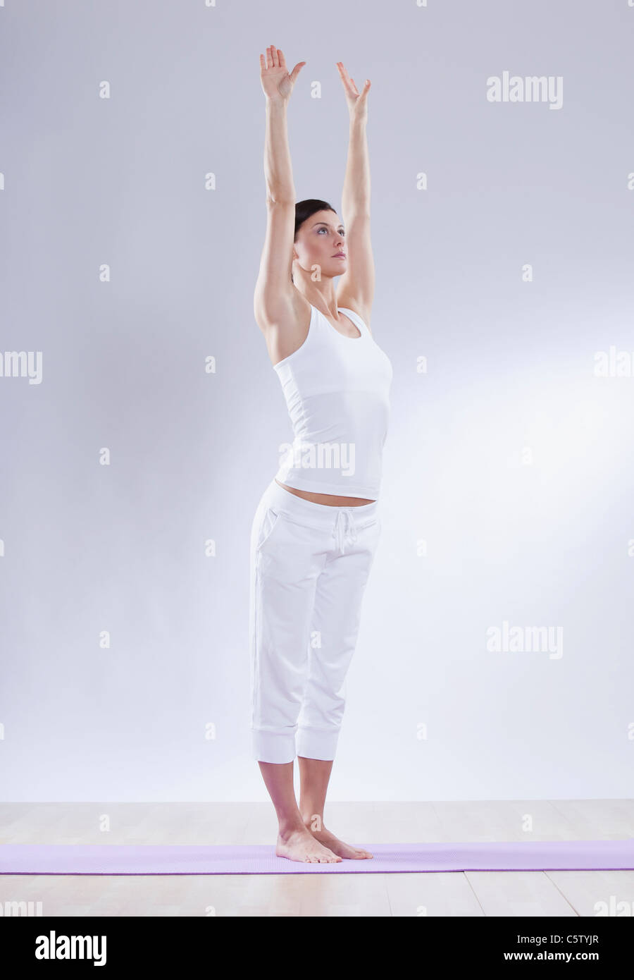 Mid adult woman in mountain pose against white background - Stock Image