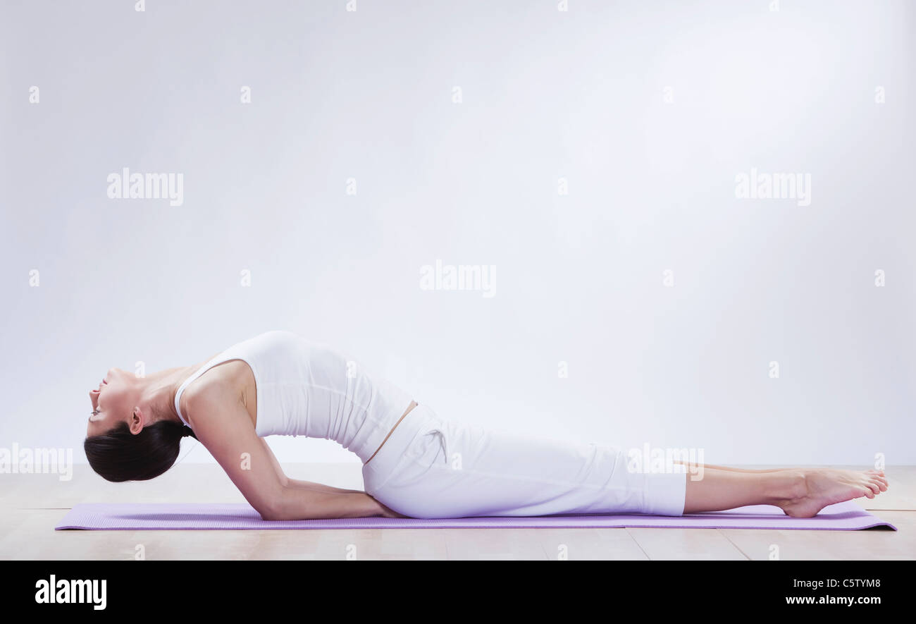 Mid adult woman doing fish pose against white background - Stock Image