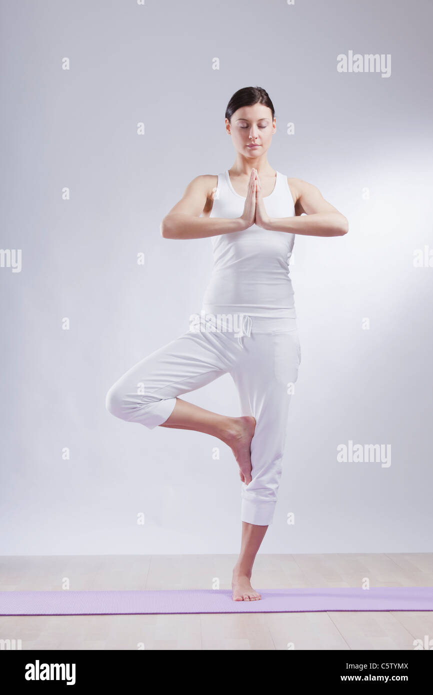 Mid adult woman in tree pose against white background Stock Photo
