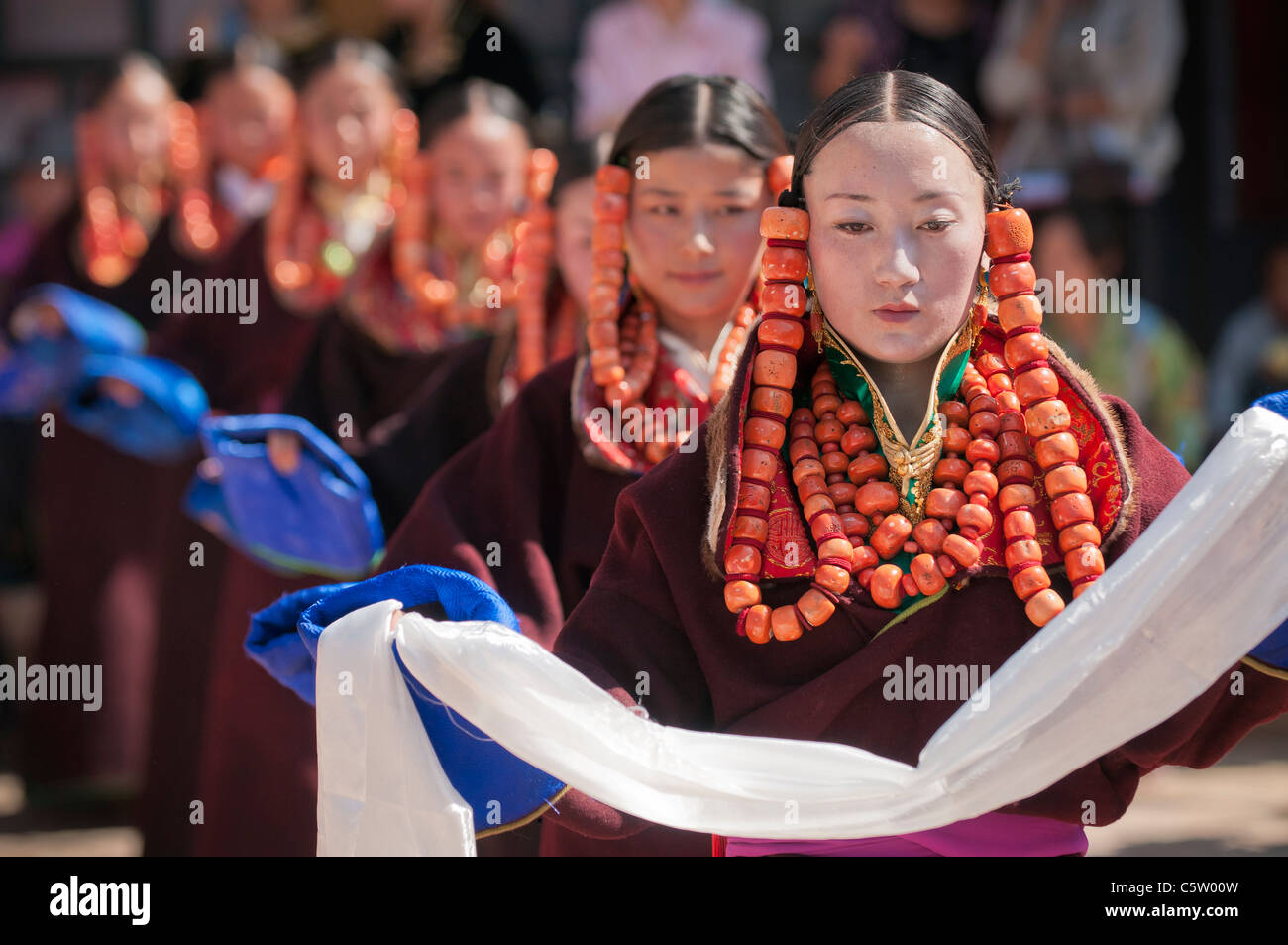 Young girls wearing heavy coral jewelry perform at shaman harvest festival, Tongren, Qinghai Province, China - Stock Image