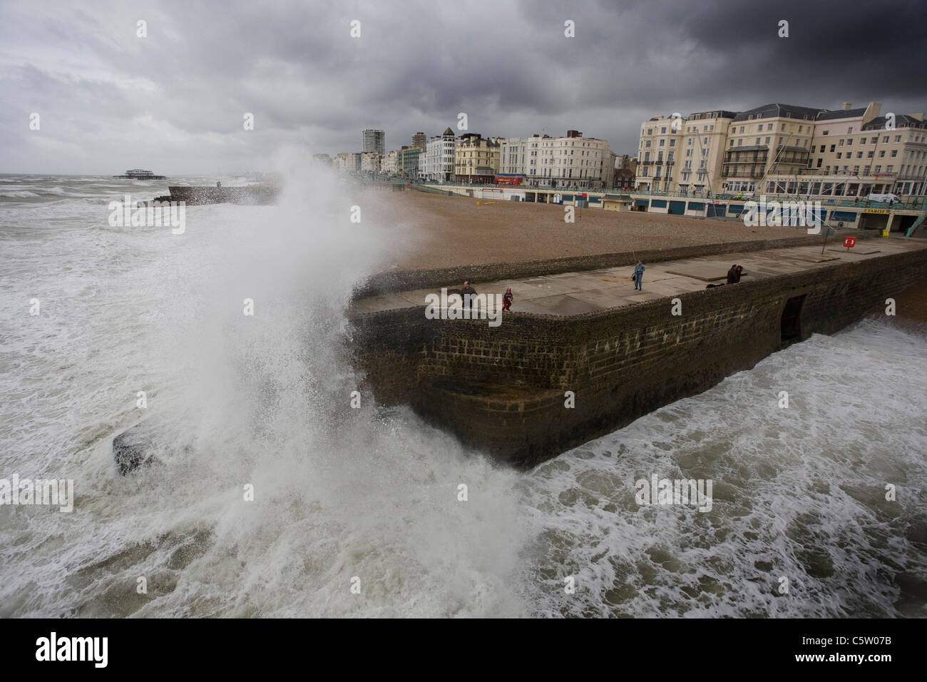 Waves crash onto a groin on Brighton beach. Picture by James Boardman - Stock Image