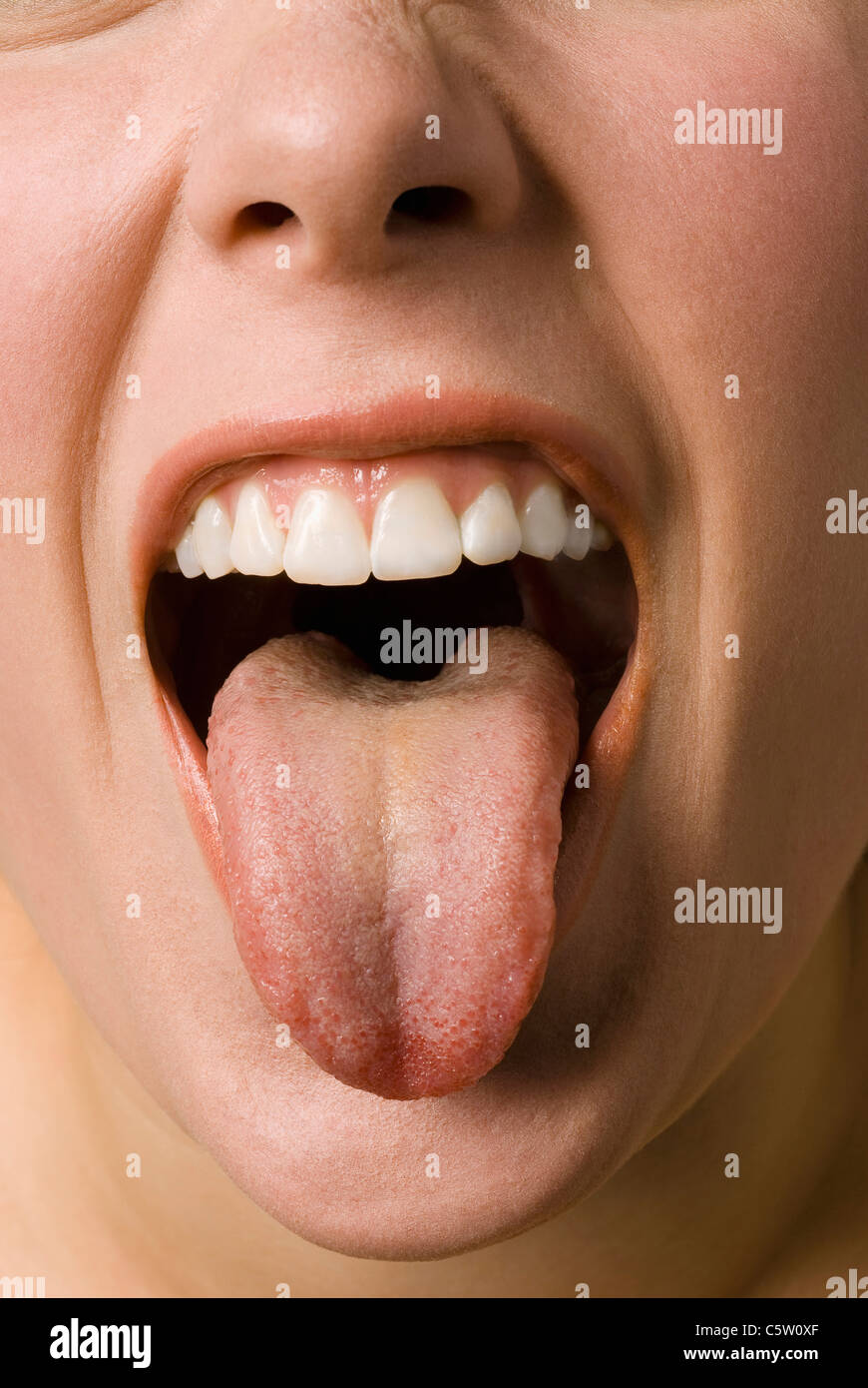 Young woman poking her tongue out, close up - Stock Image