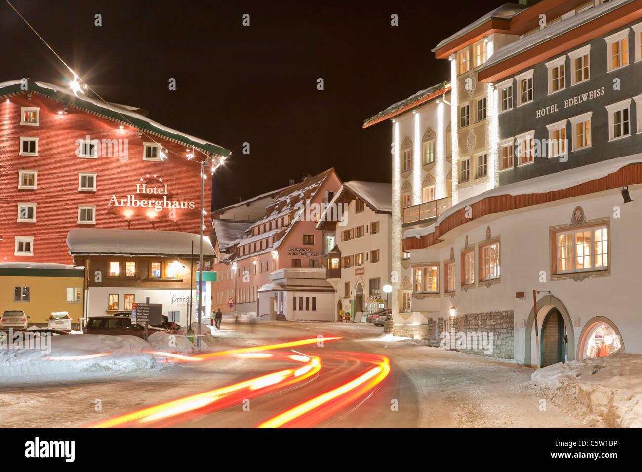 Austria, Vorarlberg, Zurs am Arlberg, View of light trail on main road near hotels in winter - Stock Image