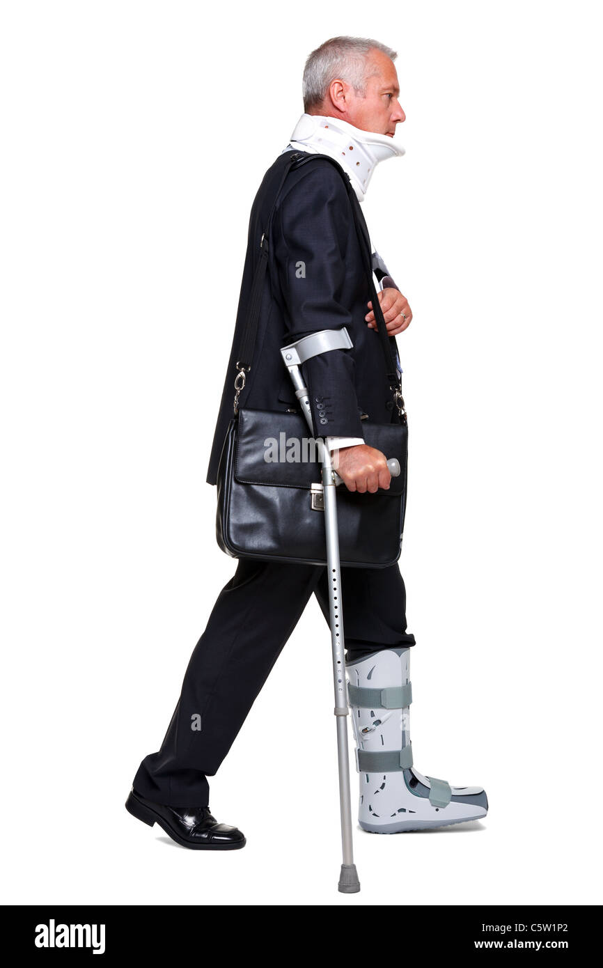 Photo of a badly injured businessman walking on cructhes carrying a briefcase, isolated on a white background. - Stock Image