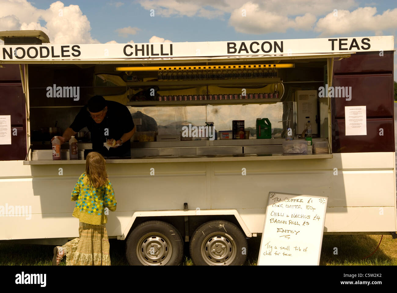 Catering trailer serving food to a customer. England UK - Stock Image