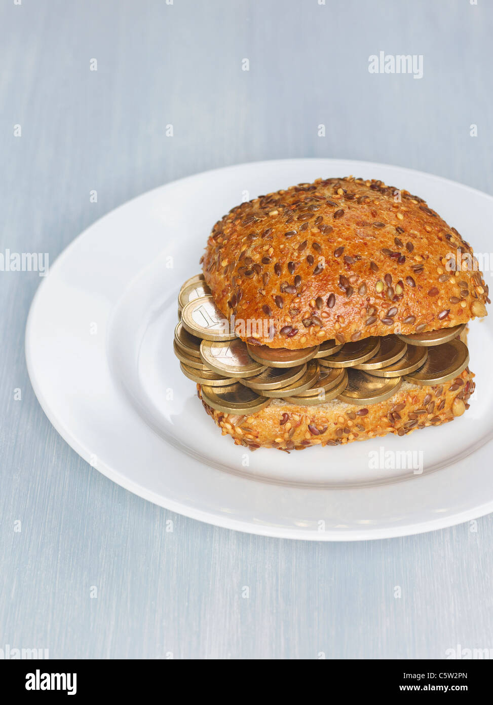 Bread roll with 1 Euro coins on plate - Stock Image
