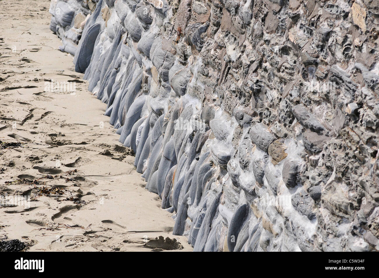 Part of the sea wall worn smooth by high tide - Stock Image