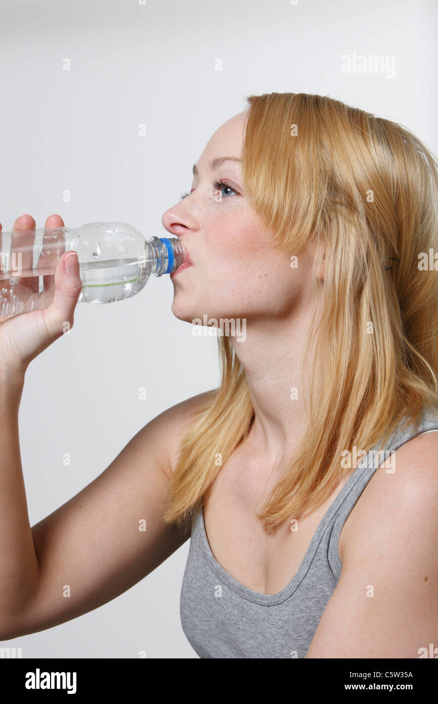 Young woman drinking from water bottle, portrait - Stock Image