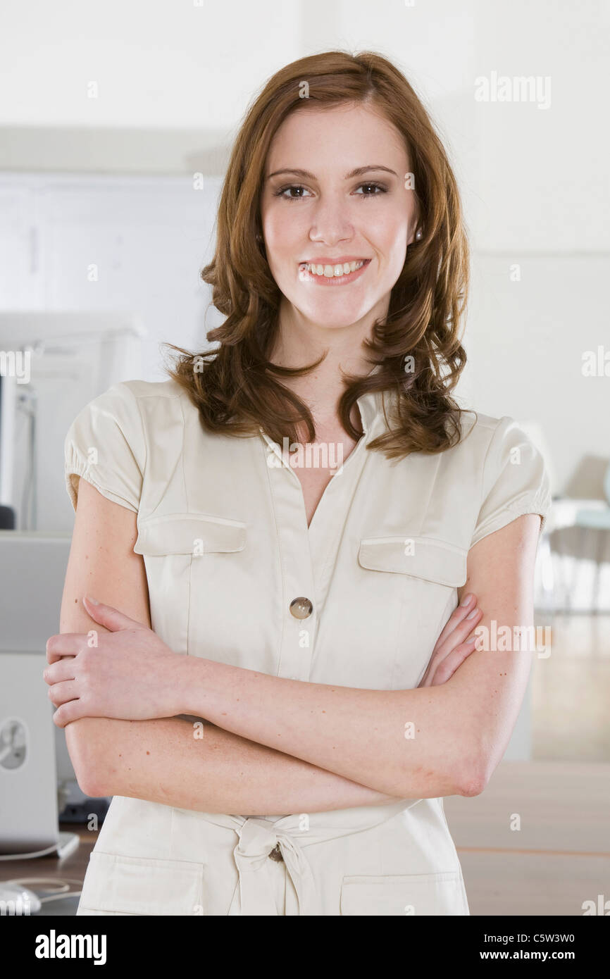 Germany, Munich, young woman in office, smiling, portrait - Stock Image