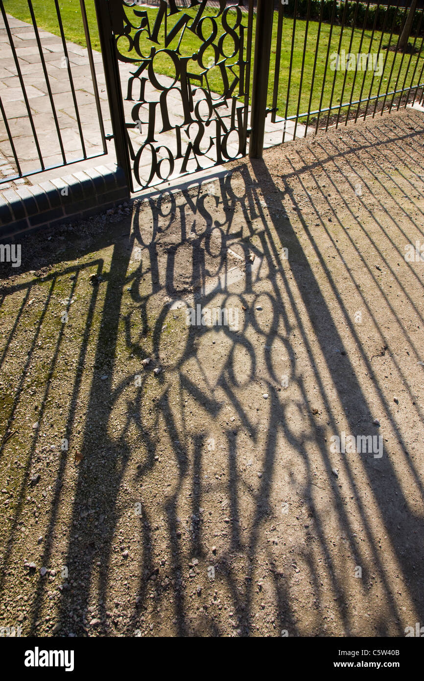 Jumble of letters in a wrought iron gate with shadow cast on