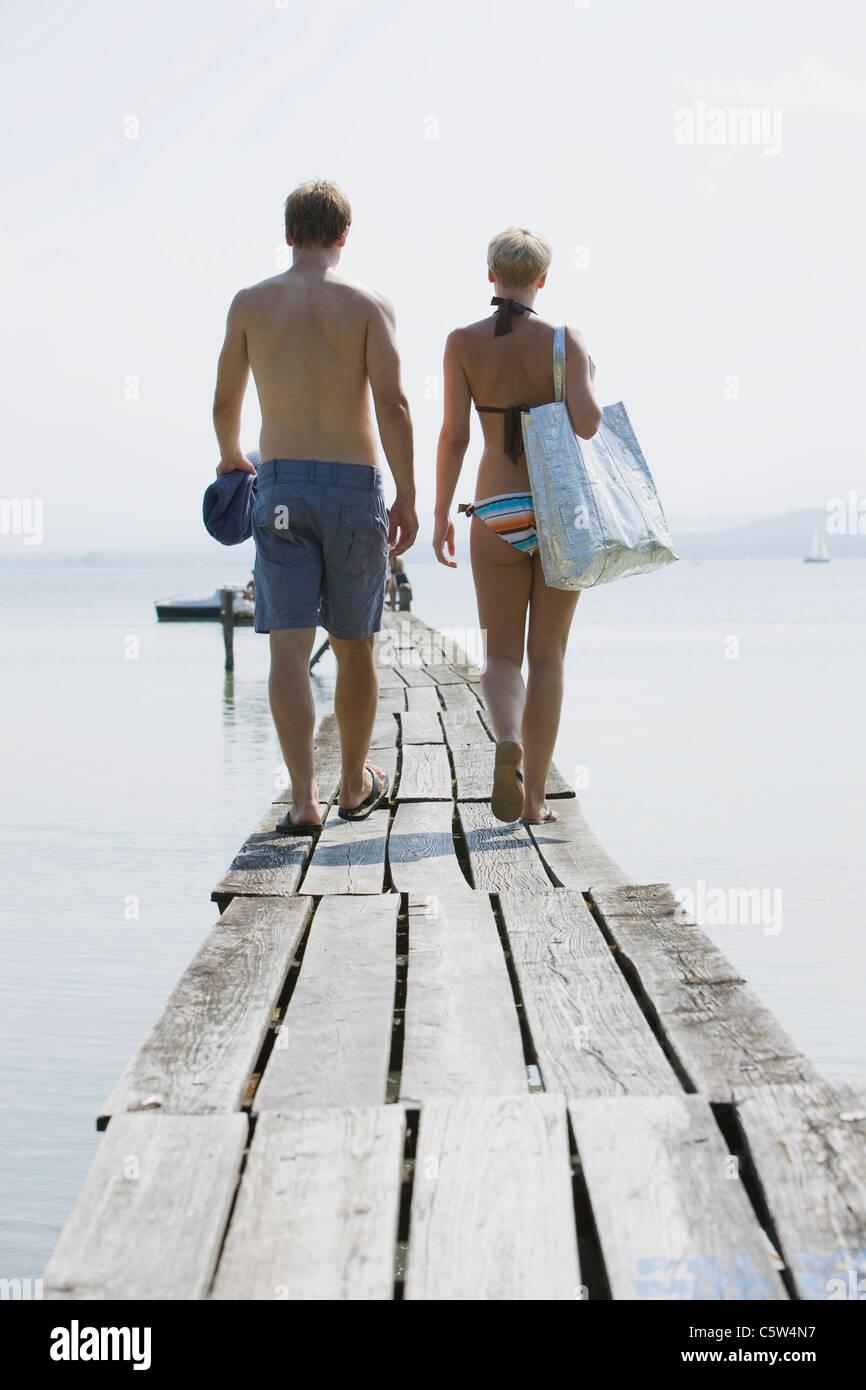 Germany, Bavaria, Young couple wearing swimwear walking on jetty, rear view - Stock Image