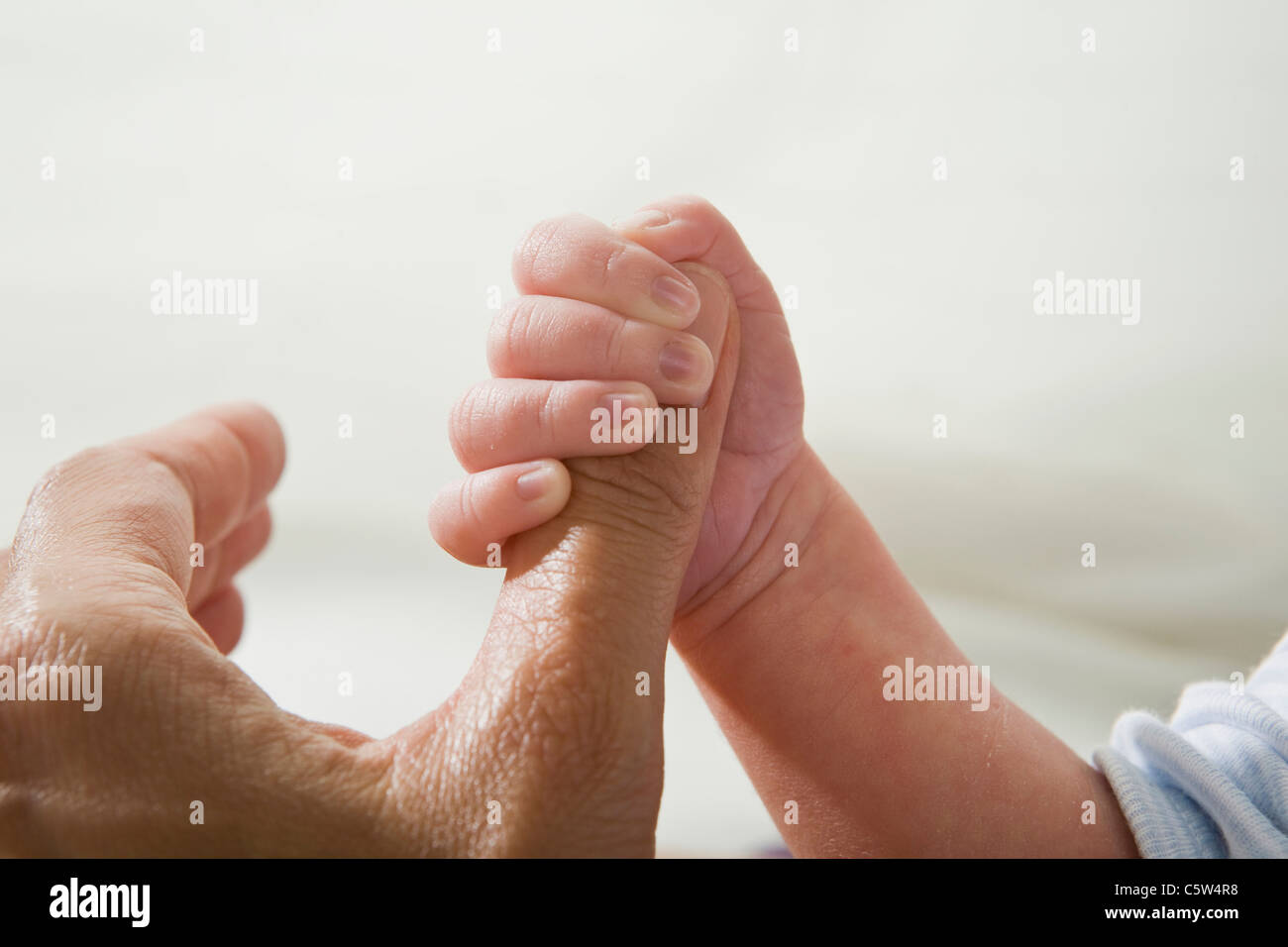 Father holding baby's hand, close-up - Stock Image