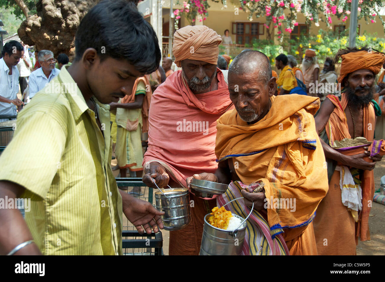 Sadu being served food Sri Ramana Ashram Tiruvannamalai Tamil Nadu South India - Stock Image