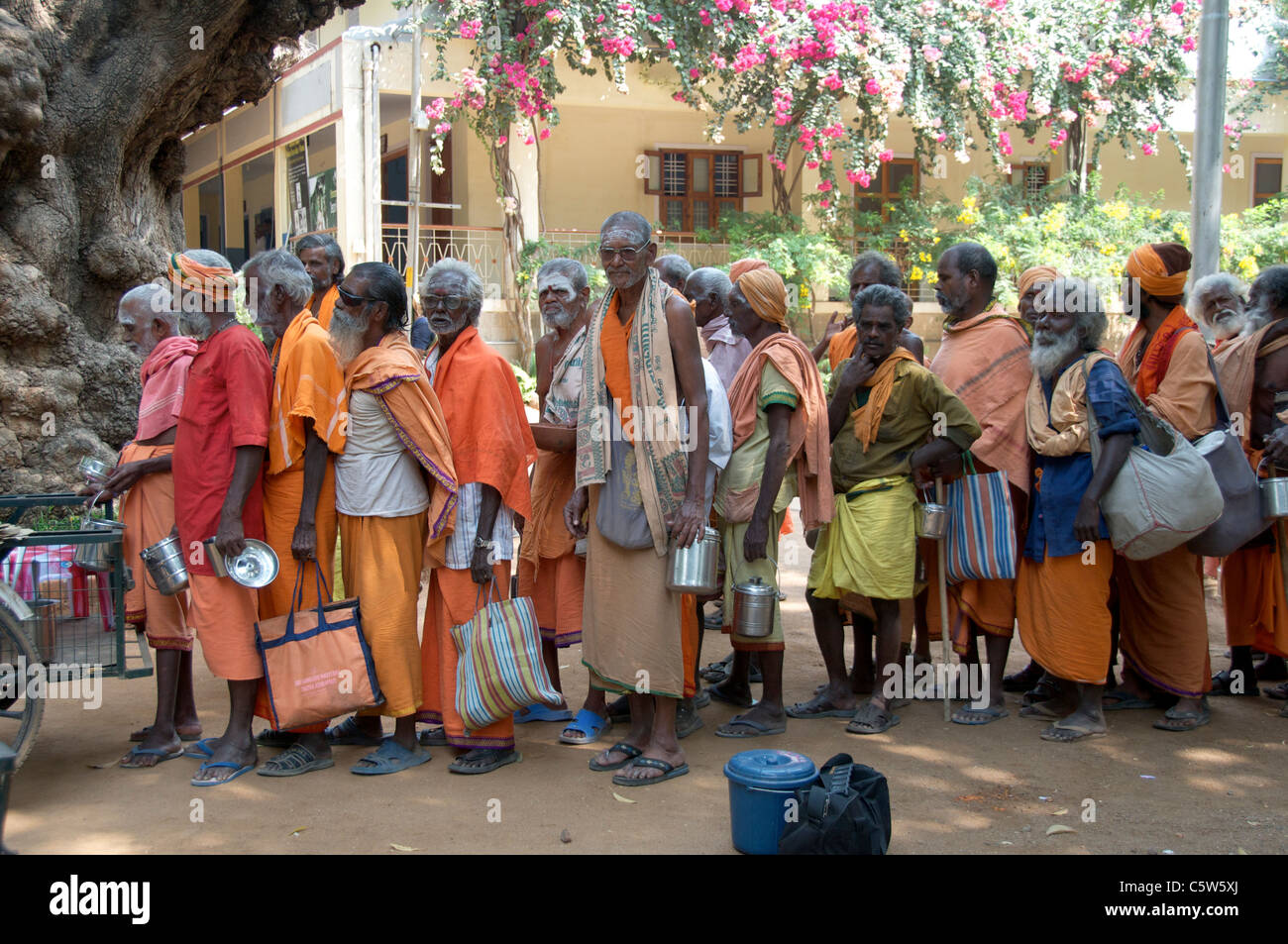 Sadhus queuing for food Sri Ramana Ashram Tiruvannamalai Tamil Nadu South India - Stock Image