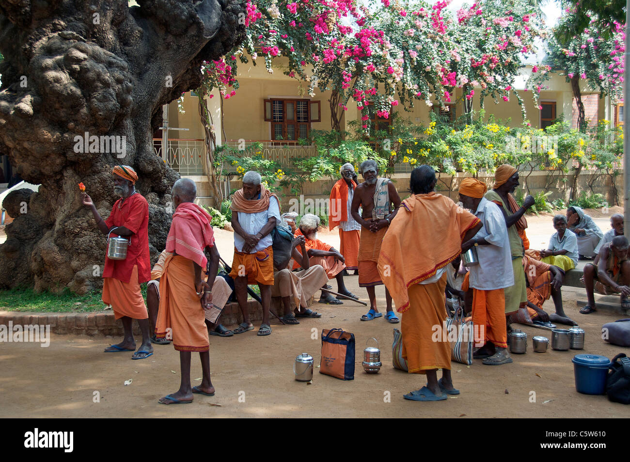Sadhus waiting for food Sri Ramana Ashram Tiruvannamalai Tamil Nadu South India - Stock Image