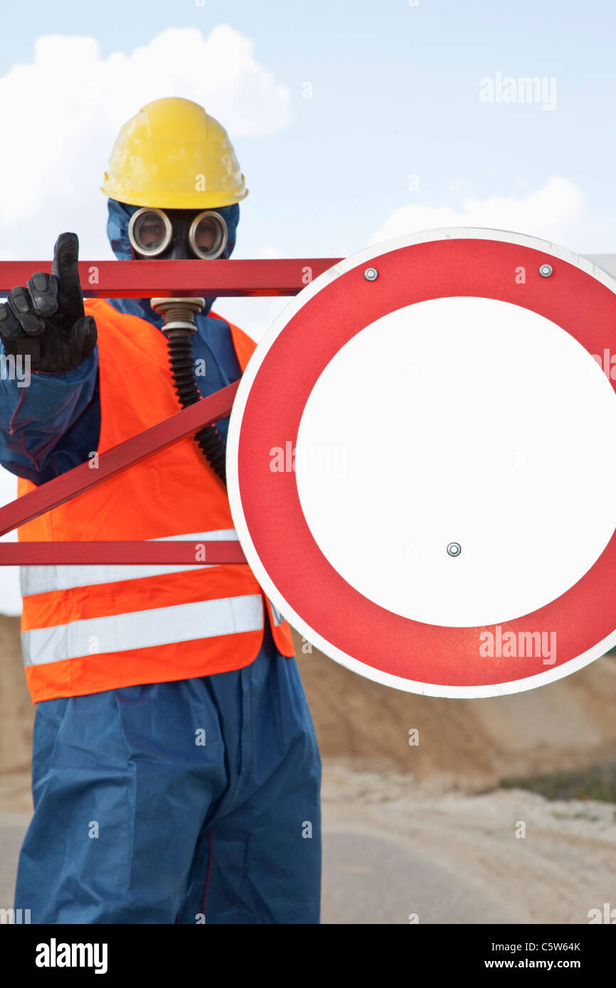 Germany, Man in protective workwear near stop sign - Stock Image