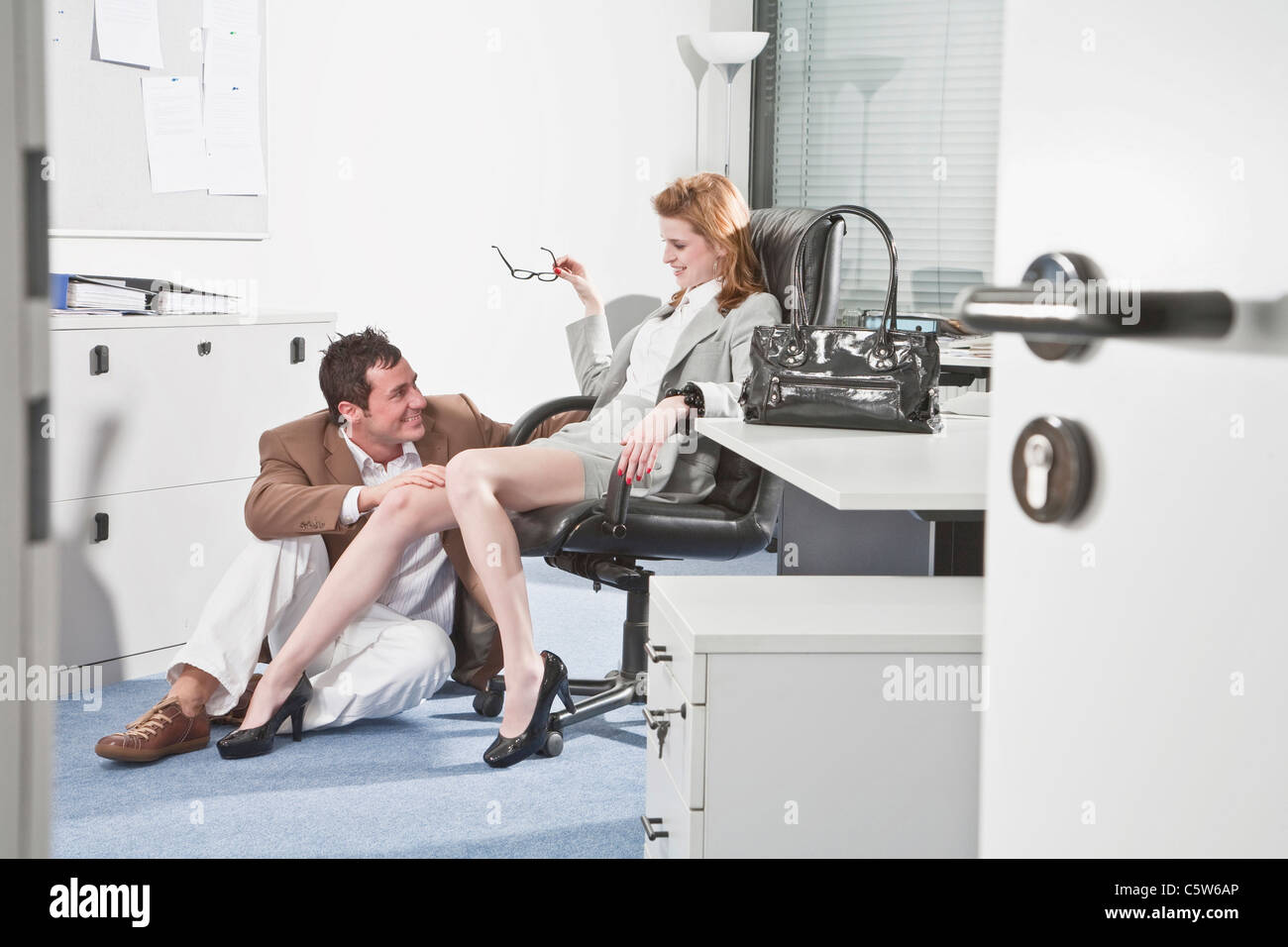 Germany, Business people in office, Business man touching woman's knee - Stock Image