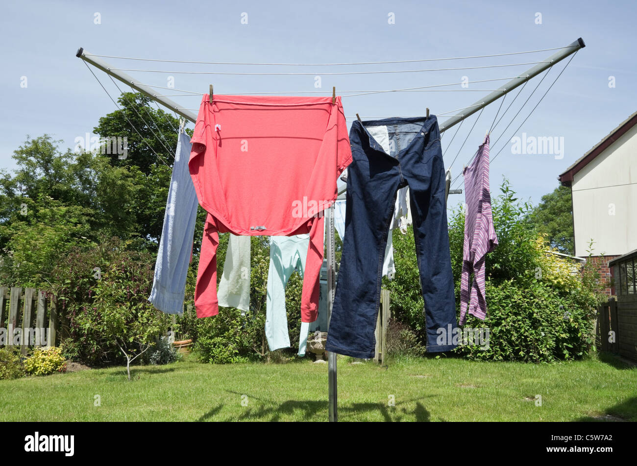 Wet clothes hanging out on a rotary washing line to dry