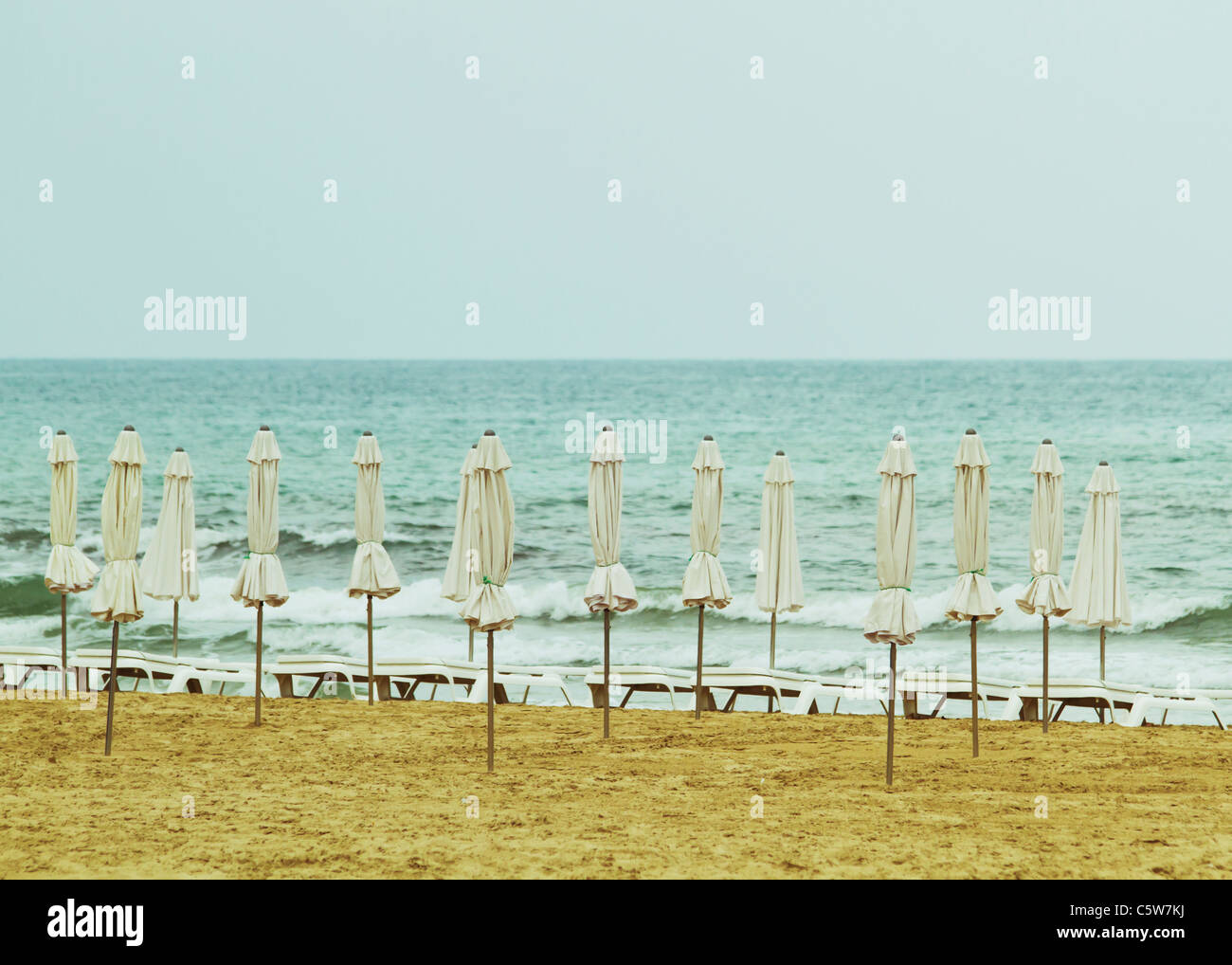 Spain, Alicante, View of empty beach with tied beach umbrellas and sun loungers - Stock Image