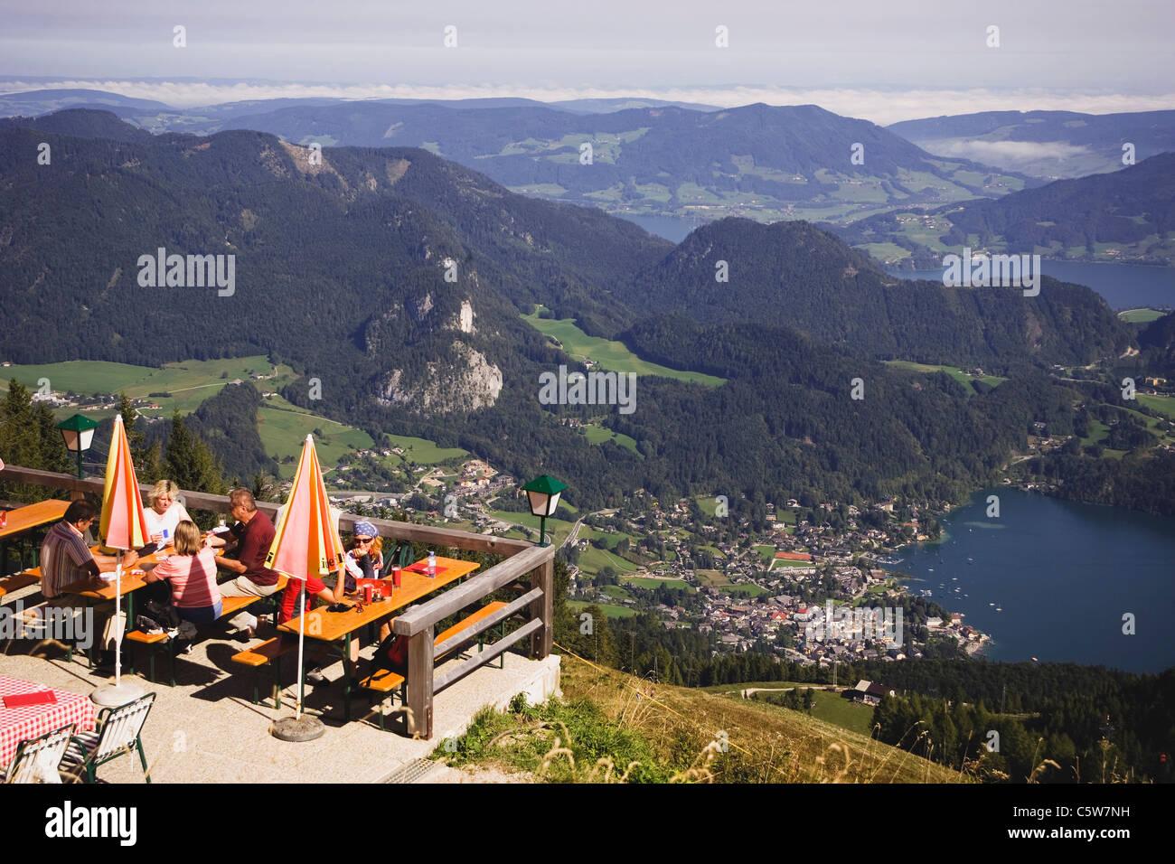 Austria, St Gilgen, Lake Wolfgangsee, Zwölferhorn, Tourists in beer garden - Stock Image