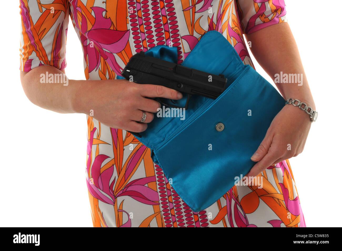Woman with a gun,  woman with handgun in her handbag - Stock Image