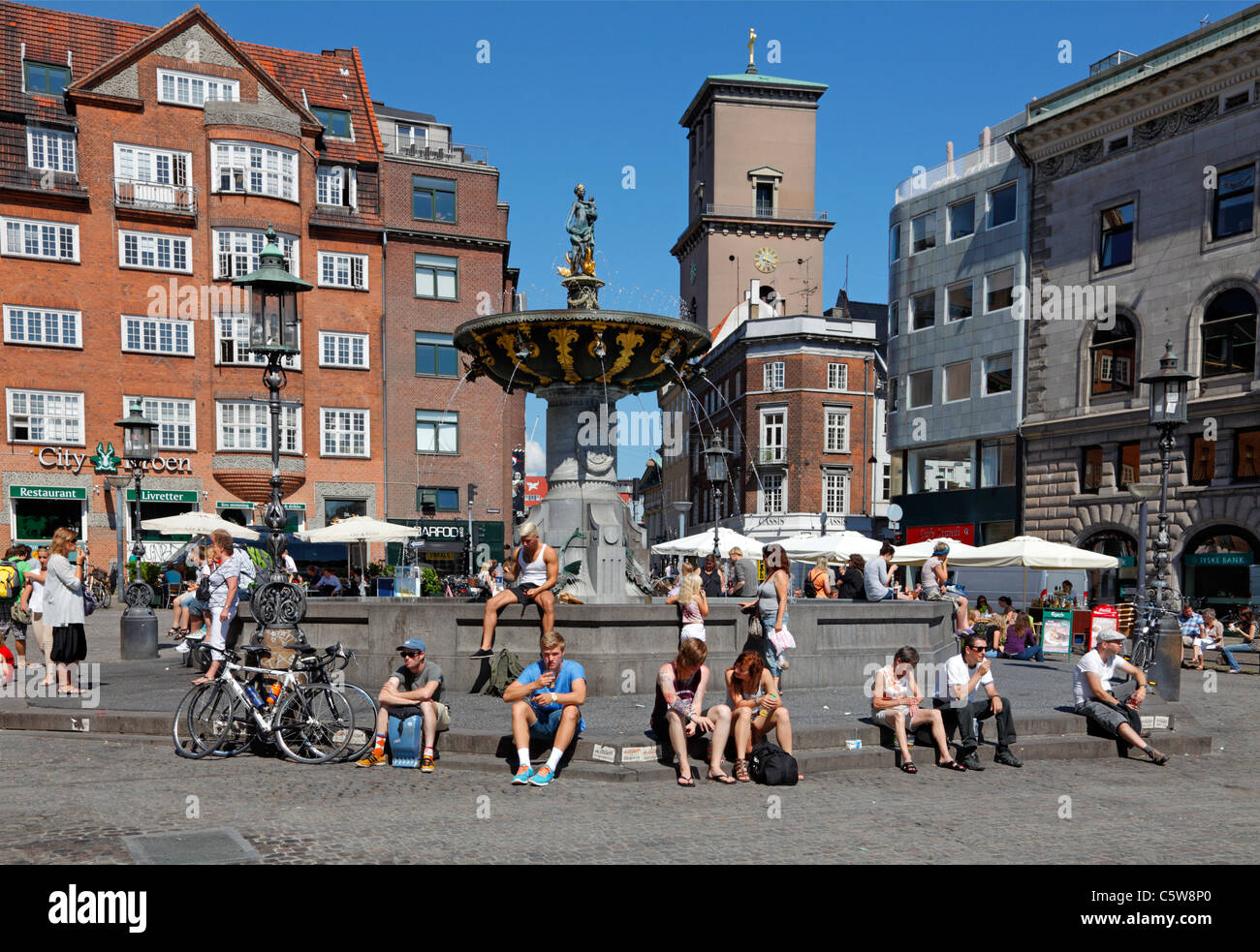 Tourists relaxing on and around the Caritas fountain at Gammeltorv on Strøget in the city of Copenhagen on - Stock Image