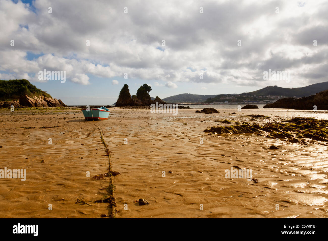 Spain, Ria de Viveiro, View of stranded boat in mub at bay - Stock Image