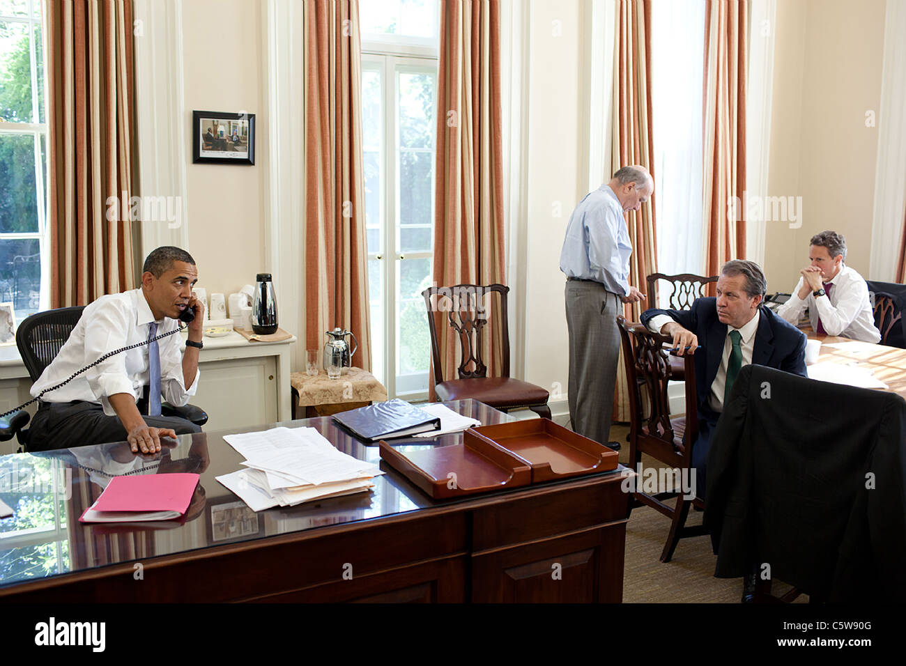 President Barack Obama talks on the phone with House Minority Leader Nancy Pelosi and Senate Majority Leader Harry - Stock Image