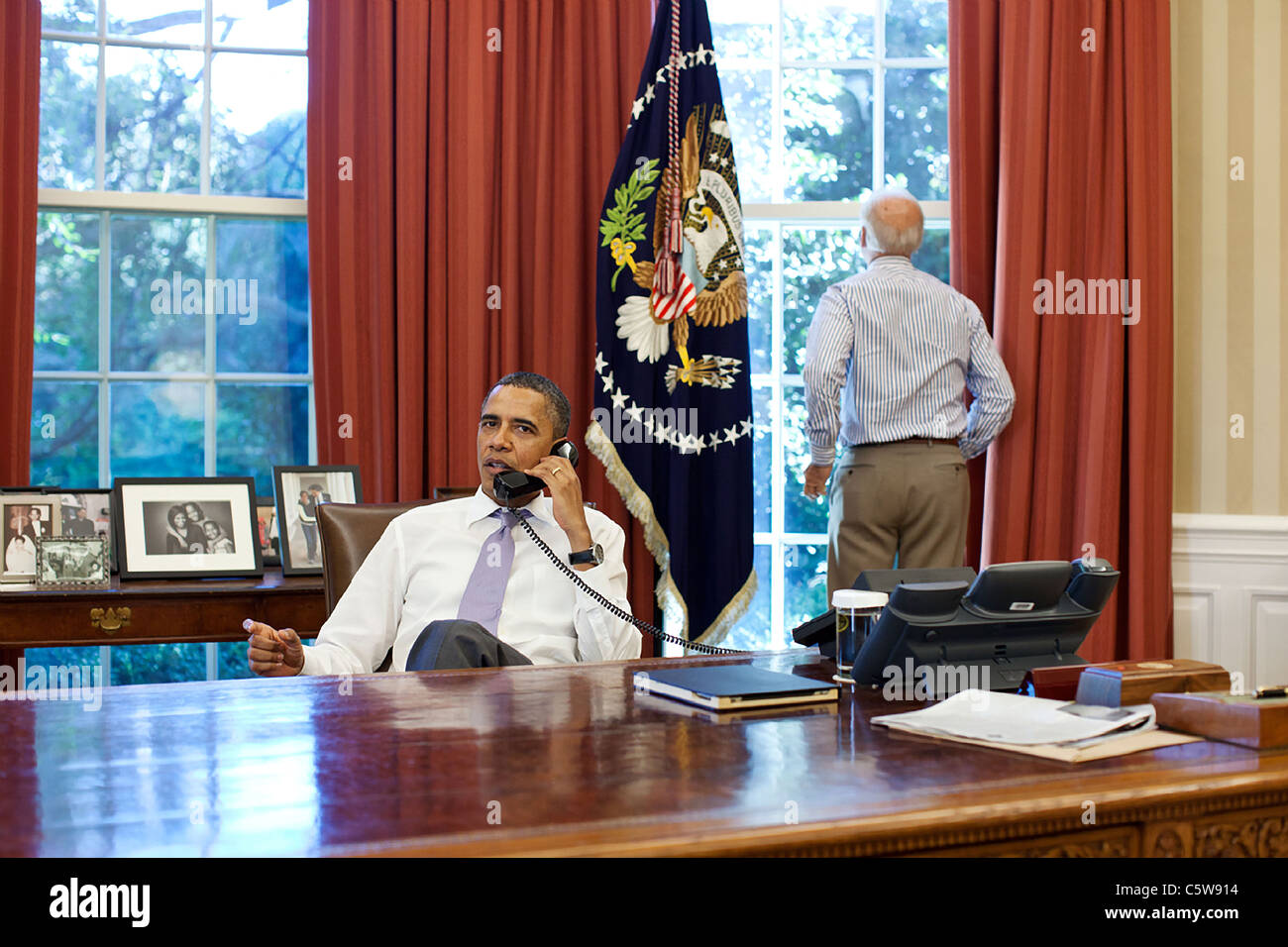 Vice President Joe Biden looks out the window as President Barack Obama talks on the phone with House Speaker John - Stock Image